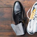 dress shoe and sneaker on wooden floor