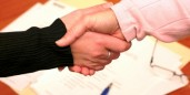 handshake over paperwork
