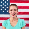 smiling woman in front of american flag