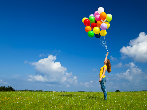 woman in a field with balloons
