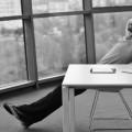 man leaning back at desk BW