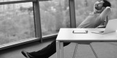 man leaning back at desk BW