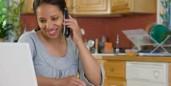 hispanic woman in kitchen laptop phone smiling