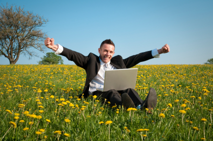 man in field flowers laptop
