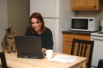 woman at kitchen table with cat laptop