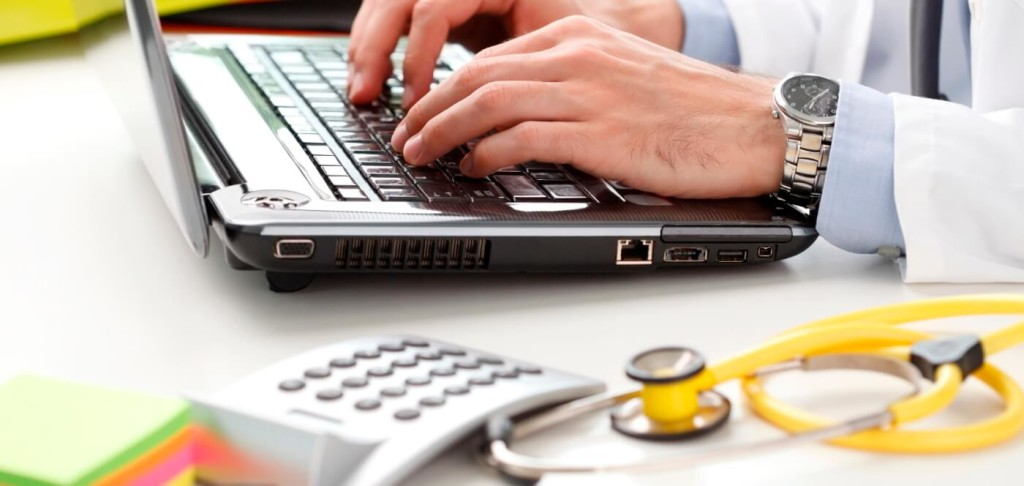 Professional looking up medical coding jobs and certifications on a laptop