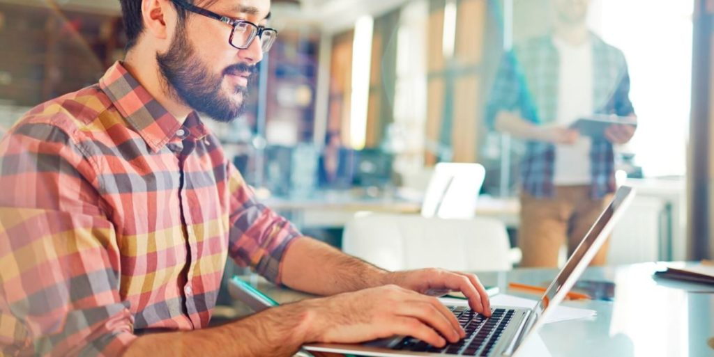 Man working on computer looking up flexible work stats