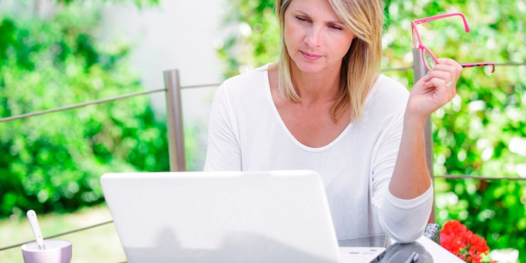 Woman searching on her laptop for legit work-from-home jobs