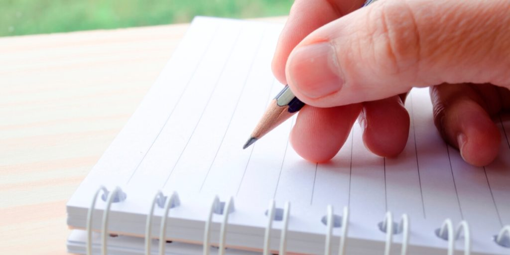Job seeker with pen and paper listing out things top job seekers do.