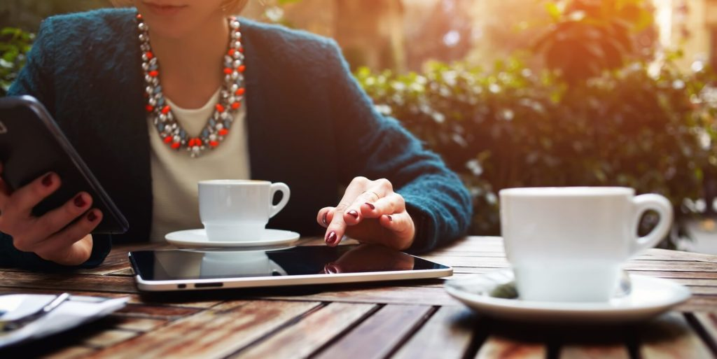 Job seeker with coffee and a smartphone, learning about the best places for a working woman.
