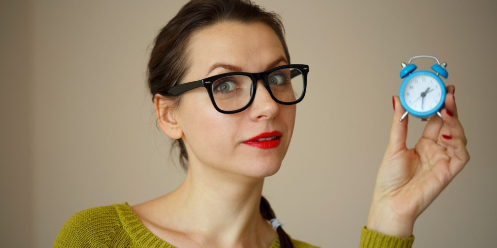 Woman job seeker holding a tiny clock and setting her time-management priorities