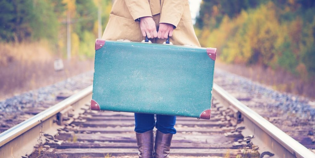 Person with a suitcase on a railroad looking for jobs for travelers