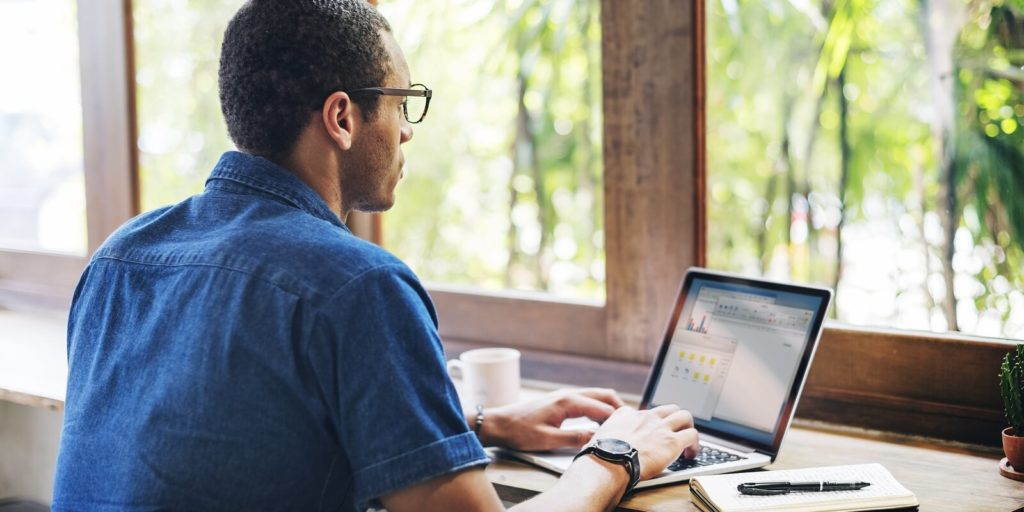 Job seeker on a laptop going through his job application checklist.
