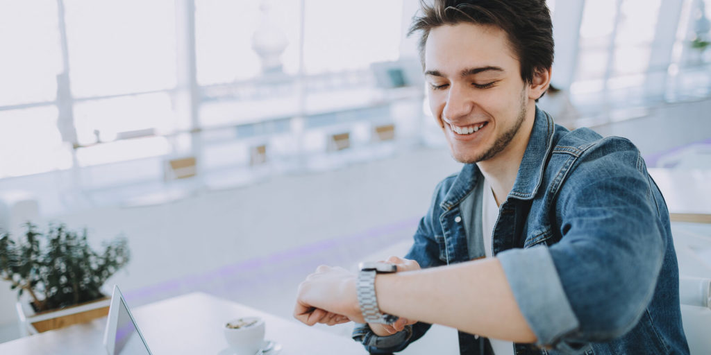 Young man checking watch tired of 9-to-5 jobs.