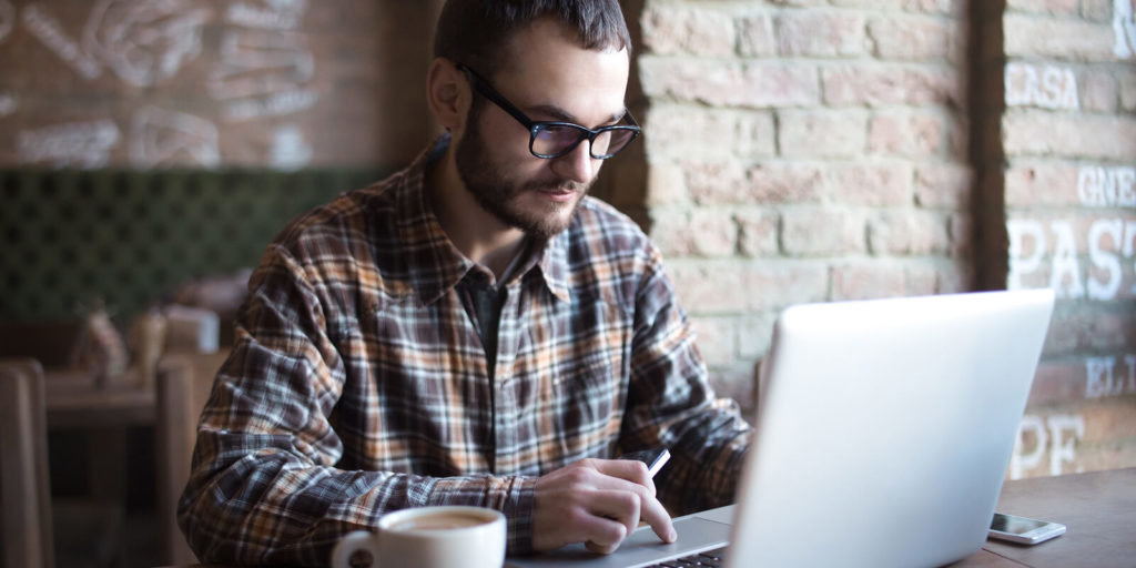 Man on laptop checking out things to do while unemployed.