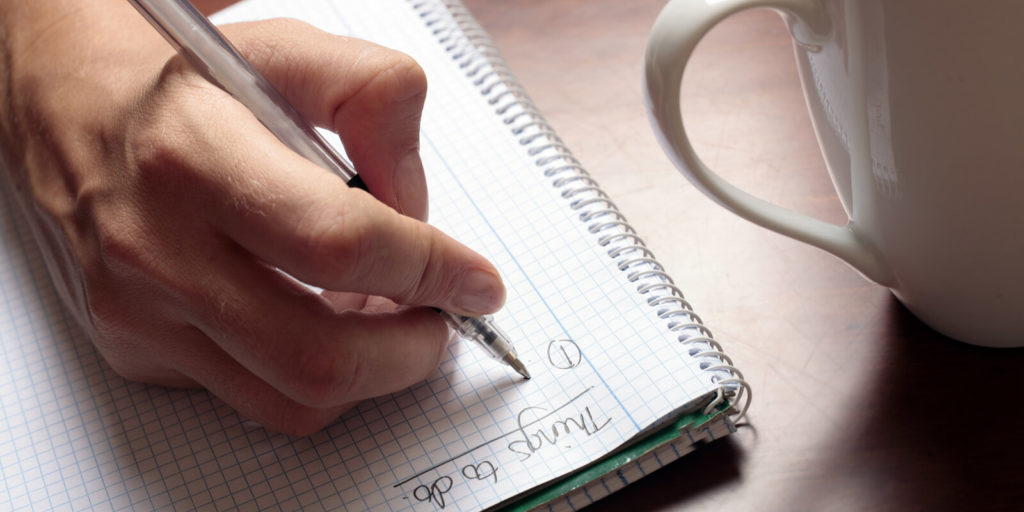 Job seeker writing down a to-do list when searching for freelance work.