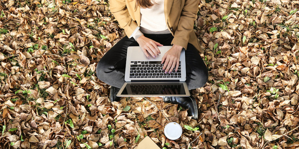 Woman working on laptop outside