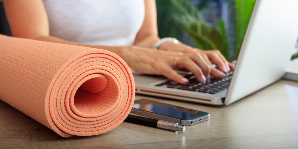Woman with a yoga mat, thriving as a remote worker