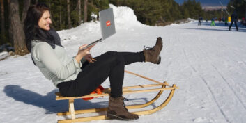 A woman on a sled holding her laptop and steering the sled.