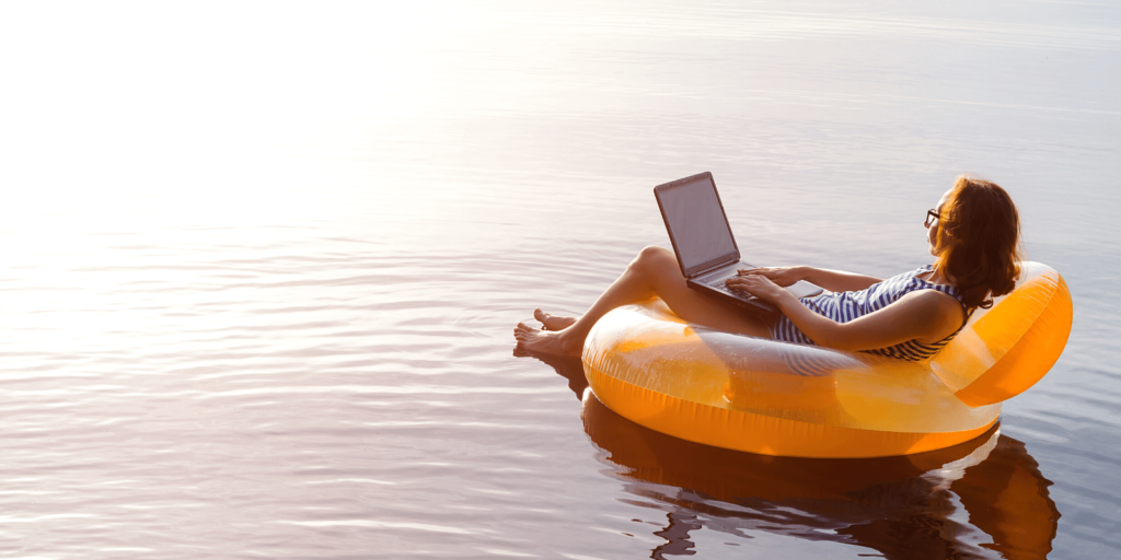 Stock photo of a woman working on her laptop while sitting in an inflatable on water