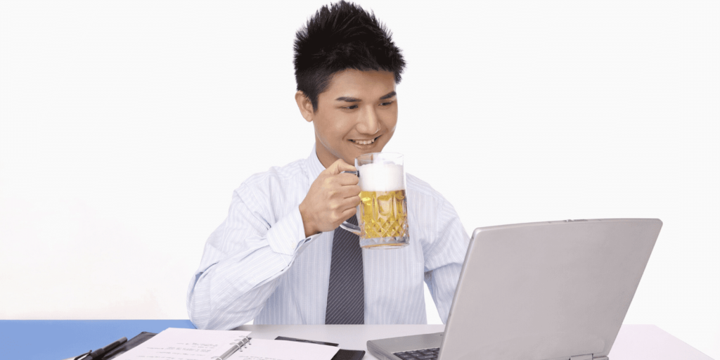 Stock photo of a man working on his laptop while drinking a beer