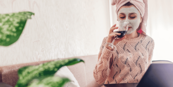 Stock photo of a woman working at home while drinking wine and giving herself a facial
