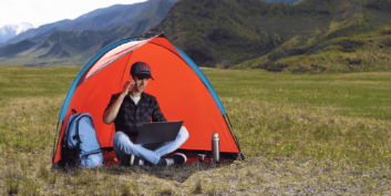 Stock photo of a man working on his laptop and talking on his phone while in a field in a tent